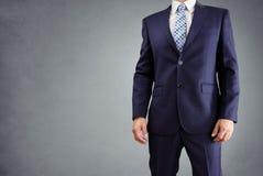 Homem de negócios em um terno isolado no fundo cinzento foto de stock royalty free