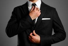 Homem de negócios em um terno preto, em uma camisa branca e em um laço Shootin do estúdio fotos de stock