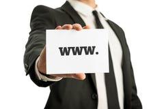 Homem de negócios em um terno que sustenta um cartão com sinal de WWW Fotografia de Stock Royalty Free