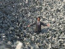 Homem de negócios em uma avalancha do dinheiro fotografia de stock royalty free