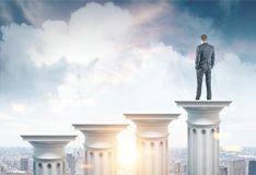 Homem de negócios em uma coluna em uma cidade imagens de stock