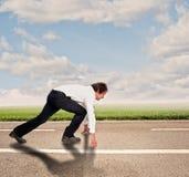 Homem de negócios em uma estrada pronto para ser executado imagem de stock