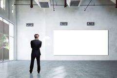 Homem de negócios em uma sala vazia com uma placa branca vazia Imagens de Stock Royalty Free