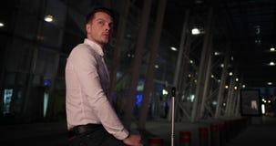 Homem de negócios em uma viagem O homem novo irritado olha seu armwatch e em torno da espera com uma mala de viagem por um táxi f video estoque