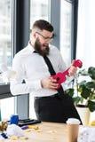 homem de negócios emocional que finge jogar a guitarra do brinquedo fotografia de stock royalty free