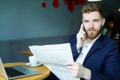 Homem de negócios encantador Reading Newspaper no café foto de stock royalty free