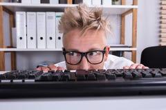 Homem de negócios engraçado Hiding Behind Desk fotos de stock