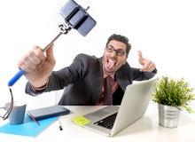 Homem de negócios engraçado na mesa de escritório que toma a foto do selfie com câmera e vara do telefone celular Fotografia de Stock Royalty Free