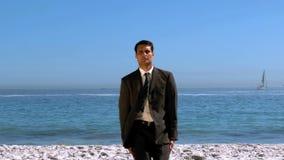 Homem de negócios engraçado que salta e que cruza a praia vídeos de arquivo