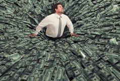 Homem de negócios engulido por um buraco negro do dinheiro Conceito da falha e da crise econômica imagens de stock royalty free
