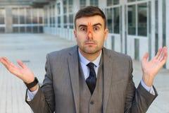 Homem de negócios enojado com o pregador de roupa em seu nariz imagem de stock