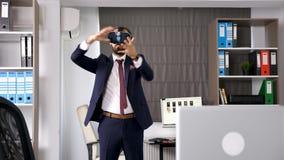 Homem de negócios ereto que veste uns auriculares de VR filme
