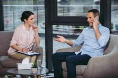 Homem de negócios de escuta do psicólogo que fala no smartphone fotografia de stock royalty free