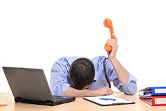 Homem de negócios esgotado que prende uma câmara de ar do telefone Fotografia de Stock Royalty Free