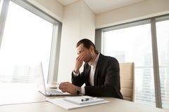 Homem de negócios esgotado que tem uma fadiga ocular após horas longas do trabalho Foto de Stock Royalty Free