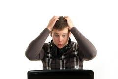 Homem de negócios espantado novo que trabalha em um portátil Fotos de Stock Royalty Free