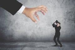 Homem de negócios estarrecente que cobre sua cara que está sendo atacada por uma mão gigante fotos de stock