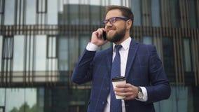 Homem de negócios europeu bem sucedido que fala no telefone celular que está no fundo moderno da construção filme