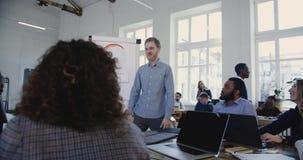 Homem de negócios europeu feliz de sorriso novo que conduz empregados incorporados multi-étnicos no seminário de treinamento das  vídeos de arquivo
