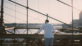 Homem de negócios europeu ocasional que está na ponte de Brooklyn usando o bracelete de relógio esperto, girando então para trás  filme
