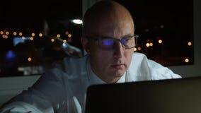 Homem de negócios executivo nos monóculos que olham o workig do portátil tarde na noite filme