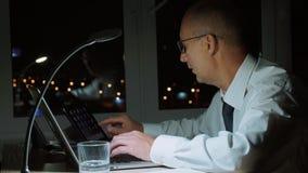 Homem de negócios executivo que trabalha tarde e que usa o portátil com tabuleta digital, retrato do perfil video estoque