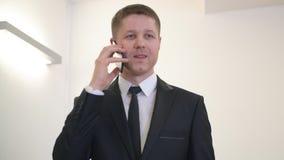 Homem de negócios executivo que usa o smartphone para a conversação móvel no escritório filme