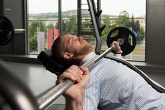 Homem de negócios Exercise Bench Press com Barbell Imagem de Stock Royalty Free