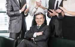 Homem de negócios experiente na idade do aplauso no fundo de seus empregados imagem de stock royalty free