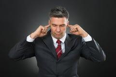 Homem de negócios With Eyes Closed e dedos em suas orelhas foto de stock