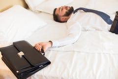 Homem de negócios Falling na cama após o dia mau fotografia de stock royalty free