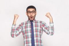 Homem de negócios farpado considerável do vencedor feliz na camisa quadriculado, bl imagem de stock royalty free
