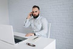 Homem de negócios farpado considerável que trabalha com o portátil no escritório e na chamada Imagem de Stock