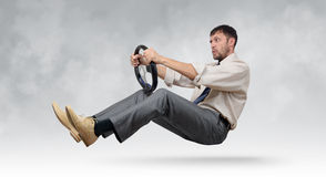 Homem de negócios farpado engraçado com um volante imagem de stock royalty free