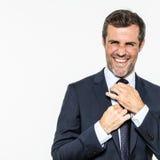Homem de negócios farpado excitado que amarra seu laço à moda que ri para a elegância imagens de stock royalty free