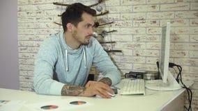Homem de negócios farpado novo com a camiseta cinzenta que trabalha no escritório brilhante vídeos de arquivo