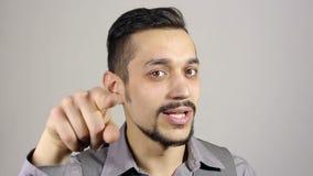 Homem de negócios farpado novo que aponta o dedo na câmera filme