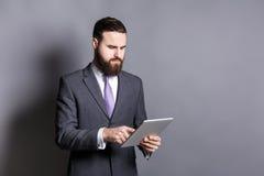Homem de negócios farpado novo que usa o tablet pc imagens de stock royalty free
