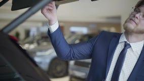 Homem de negócios farpado que escolhe o carro no fim da exposição automóvel acima O indivíduo alto inspeciona o tronco do veículo filme