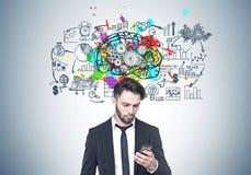 Homem de negócios farpado que olha o telefone, cérebro, rodas denteadas Fotografia de Stock