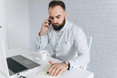 Homem de negócios farpado que senta-se em uma mesa no escritório Imagens de Stock