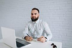 Homem de negócios farpado que senta-se em uma mesa no escritório Fotografia de Stock