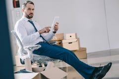 homem de negócios farpado que usa a tabuleta digital e olhando a câmera ao sentar-se fotografia de stock royalty free