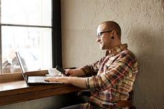 Homem de negócios farpado de sorriso que veste a roupa ocasional do moderno usando o smartphone do portátil e da pilha na casa do imagem de stock