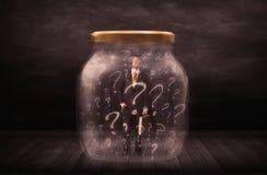 Homem de negócios fechado em um frasco com conceito dos pontos de interrogação Imagem de Stock