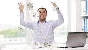 Homem de negócios feliz com dinheiro e portátil no escritório filme