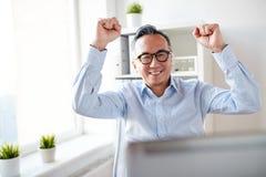 Homem de negócios feliz com o portátil no escritório Imagem de Stock Royalty Free