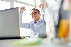 Homem de negócios feliz com o portátil no escritório Imagem de Stock