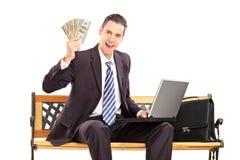 Homem de negócios feliz com o portátil que senta-se em um banco e que guarda o dinheiro Imagens de Stock
