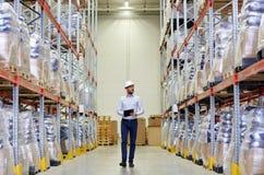 Homem de negócios feliz com a prancheta no armazém Foto de Stock